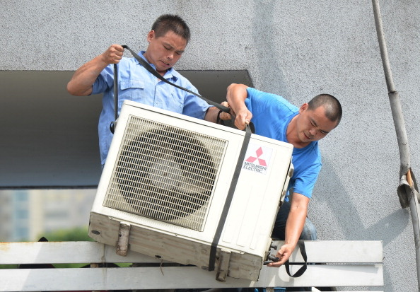 Workers install an air conditioning unit in a food stall in Shanghai on July 2, 2013.
