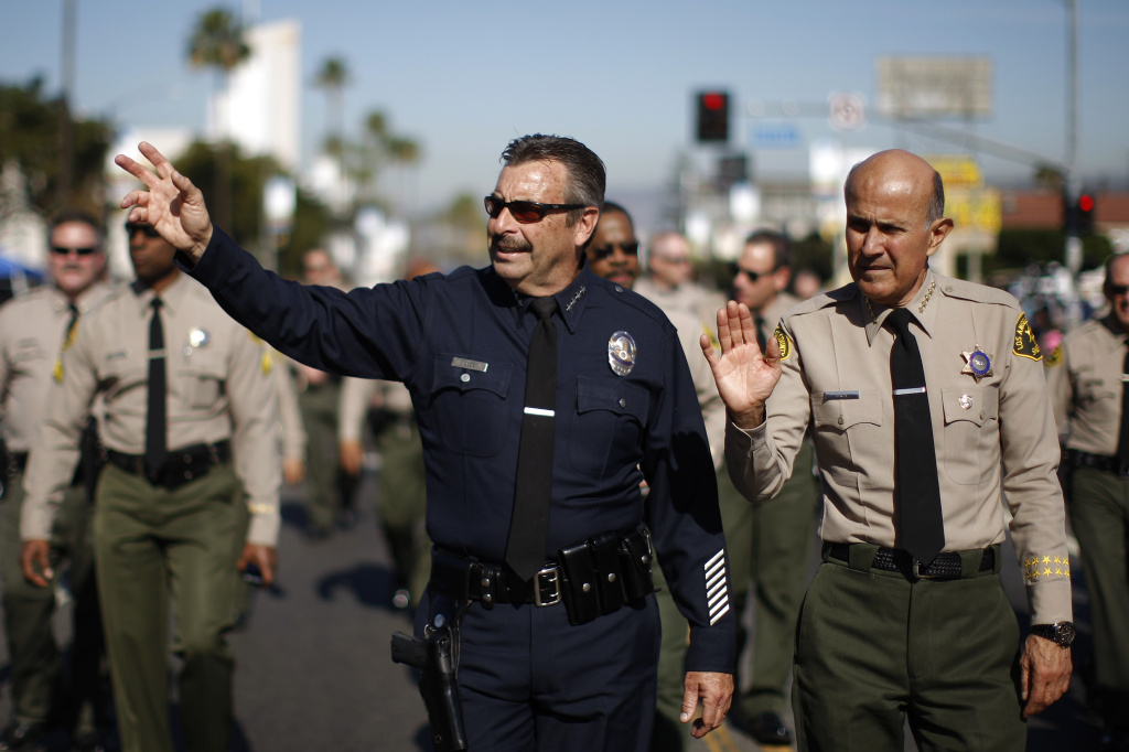 Los Angeles Police Chief Charlie Beck (L) and retiring Los Angeles County Sheriff Lee Baca march in the 29th annual Kingdom Day Parade on January 20, 2014 in Los Angeles, California.