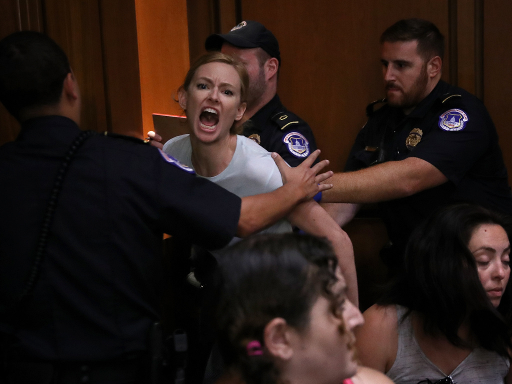 A protester is led away by police after disrupting the second day of the confirmation hearing for Supreme Court nominee Judge Brett Kavanaugh on Capitol Hill on Sept. 5, 2018.