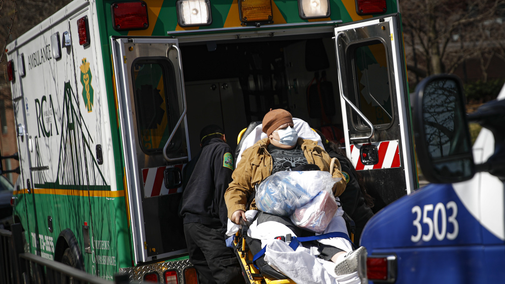 Medical workers load a patient wearing a protective mask into the back of an ambulance Wednesday outside a hospital in Brooklyn. New York has seen a spike in coronavirus cases, and officials are preparing for an influx at medical centers throughout the state.