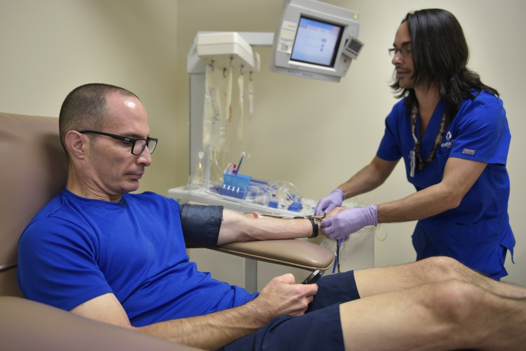 File: A technician prepares to take a platelet donation from Stephen Ruiz at the Oneblood blood center on June 13, 2016 in Orlando, Florida.