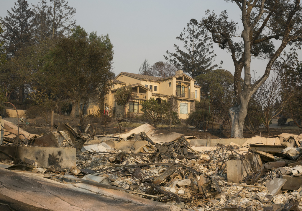 A large home that survived last week's wildfire sits by the burned ruins of a nearby home, Monday, Oct. 16, 2017, in Santa Rosa, Calif. A new blaze broke out in the Santa Cruz mountains Monday night.