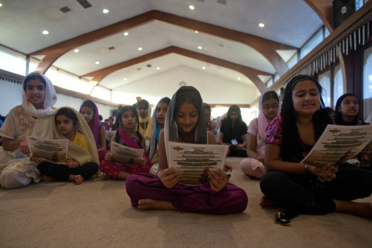 Nine-year-old Priya Singh, center, sings chants with others at the Khalsa Care Foundation on Monday, August 6.
