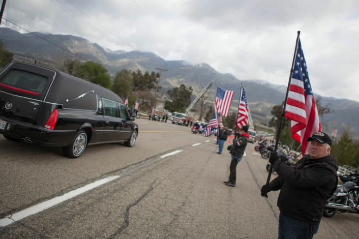 Members of a motorcycle club hold flags in salute of fallen San Bernardino Sheriff's Det. Jeremiah MacKay outside the entrance to San Miguel Amphitheater on Feb. 21, 2013.