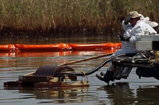 Contract workers from BP use skimmers to clean oil from a marsh near Pass a Loutre on June 1, 2010 near Venice, Louisiana.