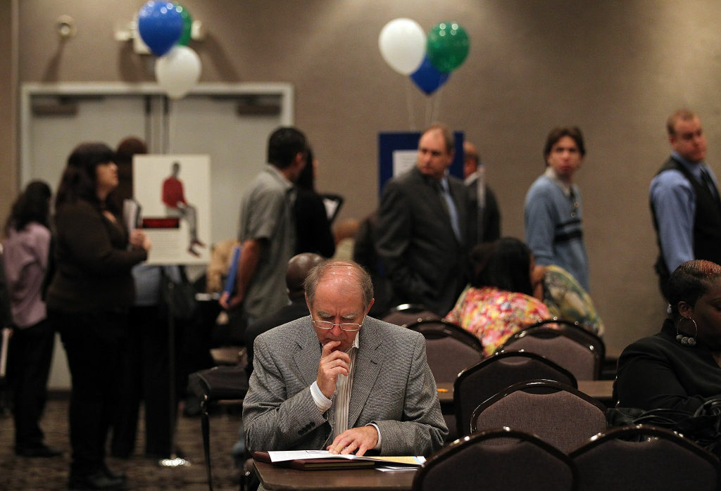 A job seeker pauses as he fills out an application during a career fair in Concord, California.