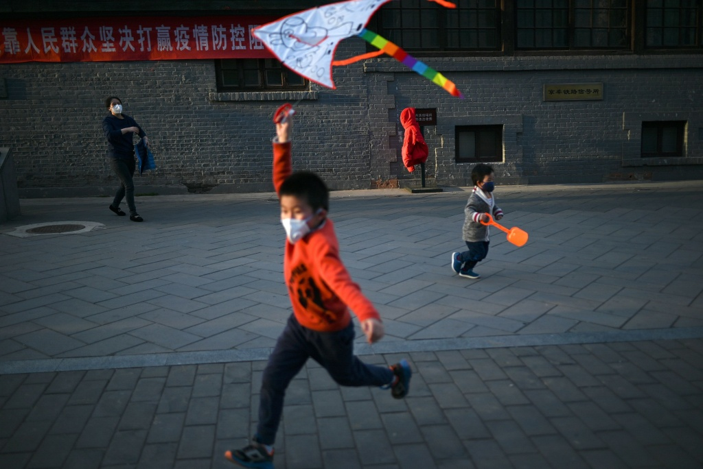 A boy wearing a facemask amid concerns over the spread of the COVID-19, flies a kite at a park in Beijing. Researchers are studying the response of children to the novel coronavirus.