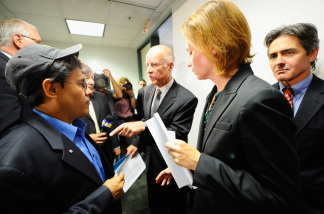 California Attorney General Jerry Brown (C) asks his deputy Susan Leach (2nd R) to speak with a city of Bell resident Nestor Valencia (2nd L) after a news conference where he announced his office has issued subpoenas on July 26, 2010 in Los Angeles, California.