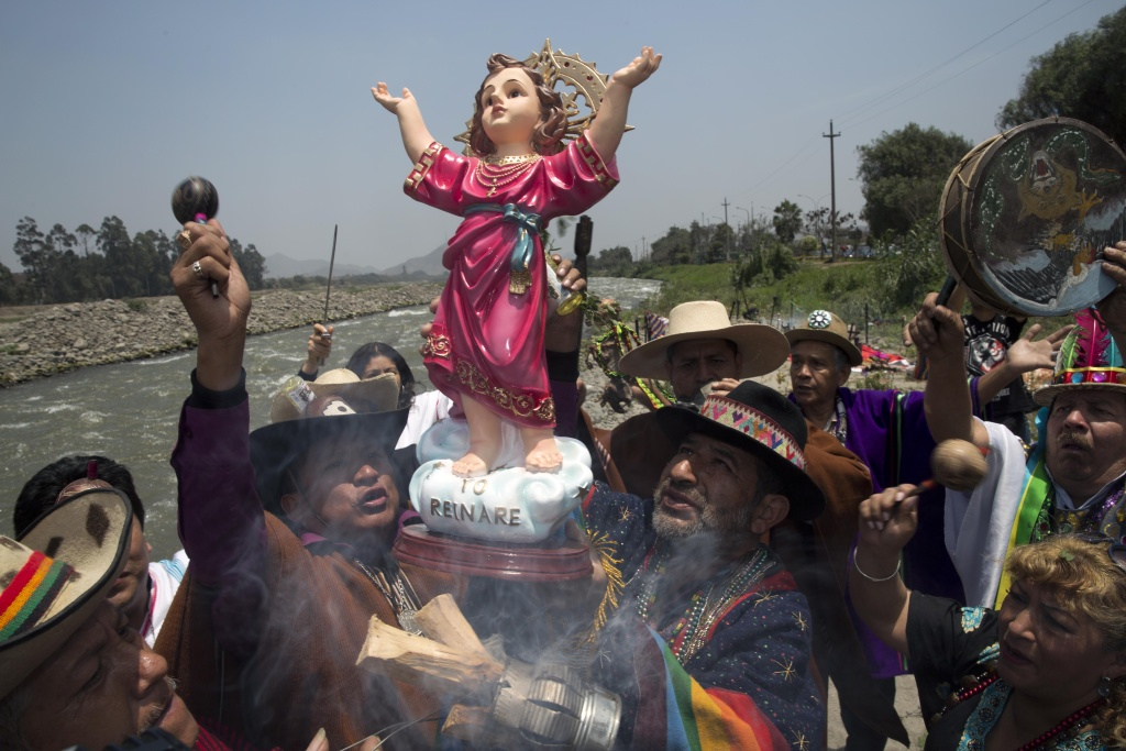Shamans near Lima, Peru, hold up a statue of the baby Jesus, or