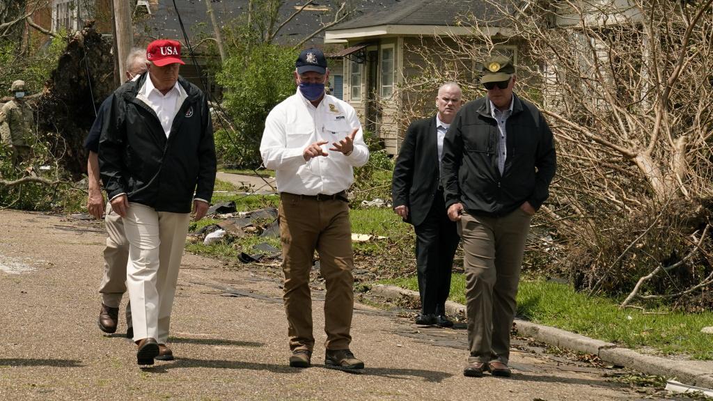 President Trump listens to Louisiana Gov. John Bel Edwards, center, as he tours damage from Hurricane Laura, in Lake Charles, La.
