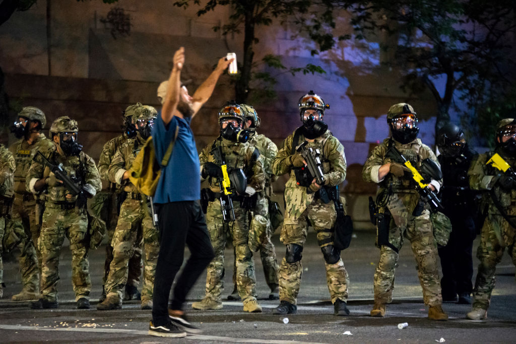 A protester holds his hands in the air while walking past a group of federal officers during a protest in front of the Mark O. Hatfield U.S. Courthouse on July 21, 2020 in Portland, Ore.