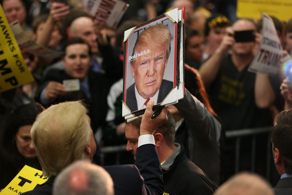 Donald Trump holds a picture of himself after being given it as he greets people during a campaign event at the University of Iowa on January 26, 2016 in Iowa City, Iowa.