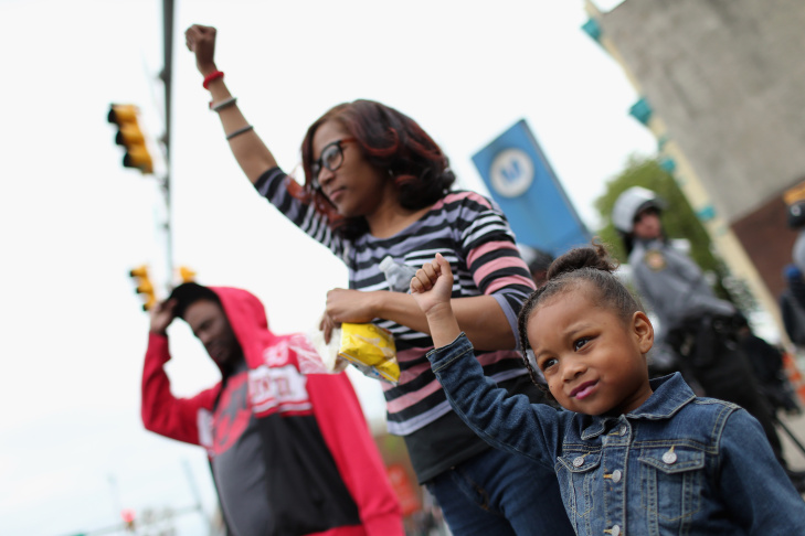 A young girl raises her fist along with others after Baltimore authorities released a report on the death of Freddie Gray on May 1, 2015, in Baltimore, Maryland. Marilyn Mosby, Baltimore City state's attorney, ruled the death of Freddie Gray a homicide and that criminal charges will be filed. Gray, 25, was arrested for possessing a switch blade knife April 12 outside the Gilmor Houses housing project on Baltimore's west side. According to his attorney, Gray died a week later in the hospital from a severe spinal cord injury he received while in police custody.