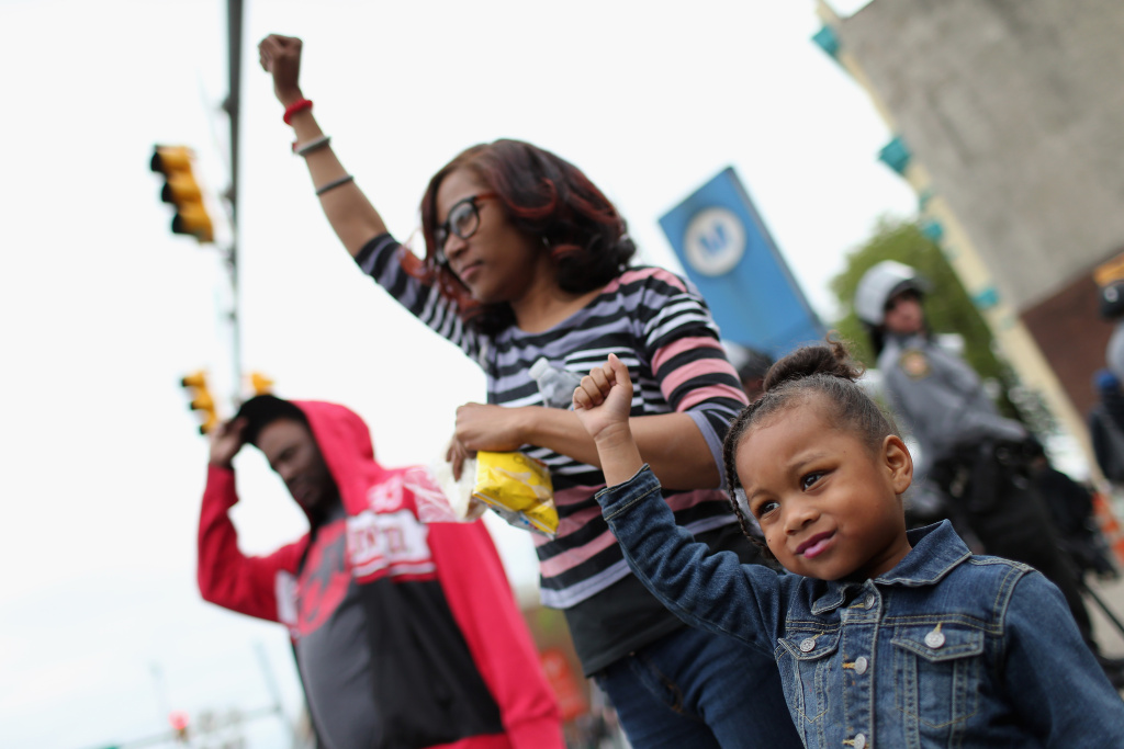 A young girl raises her fist along with others after Baltimore authorities released a report on the death of Freddie Gray on May 1, 2015