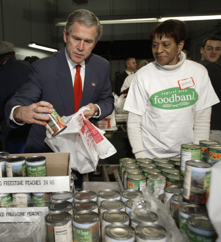 President George W. Bush grabs a can of peaches as he helps load bags of donated food for the needy collected by at least 29 federal agencies for the Capital Area Food Bank Dec. 19, 2002, with volunteer Verona Canty in Washington, DC. A writer for Slate thinks charitable organizations are better served with cash rather than cans.