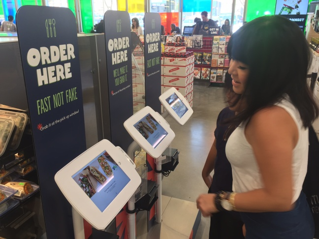 At 365 by Whole Foods, customers order many items at computerized kiosks. The store has fewer employees than typical markets.