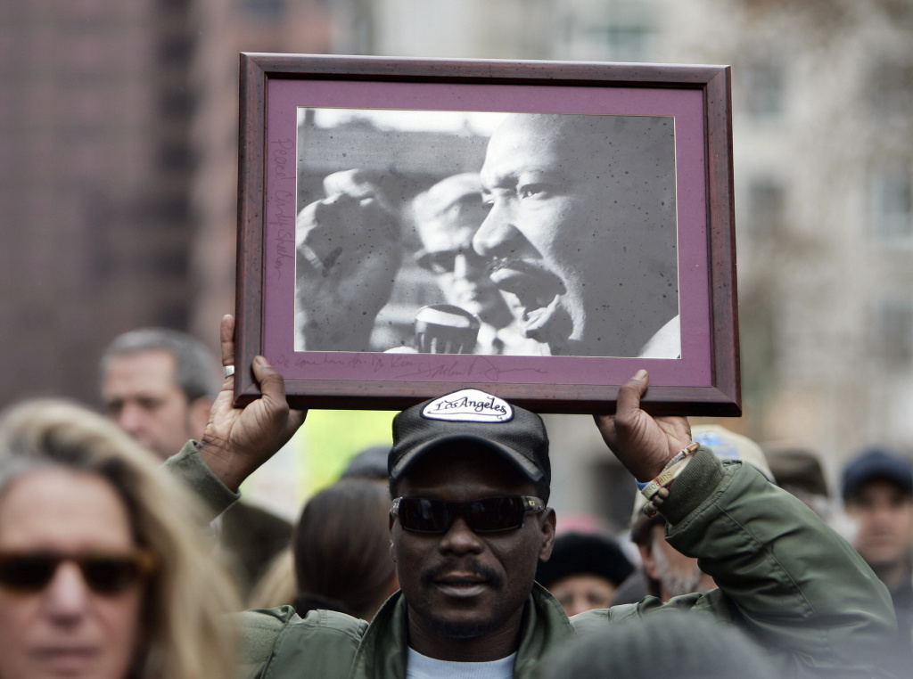 A man holds a portait of Dr. Martin Luther King, Jr., during demonstration against the war in Iraq asking US President George W. Bush to bring US troops home and to stop funding the war, Los Angeles, 2007.