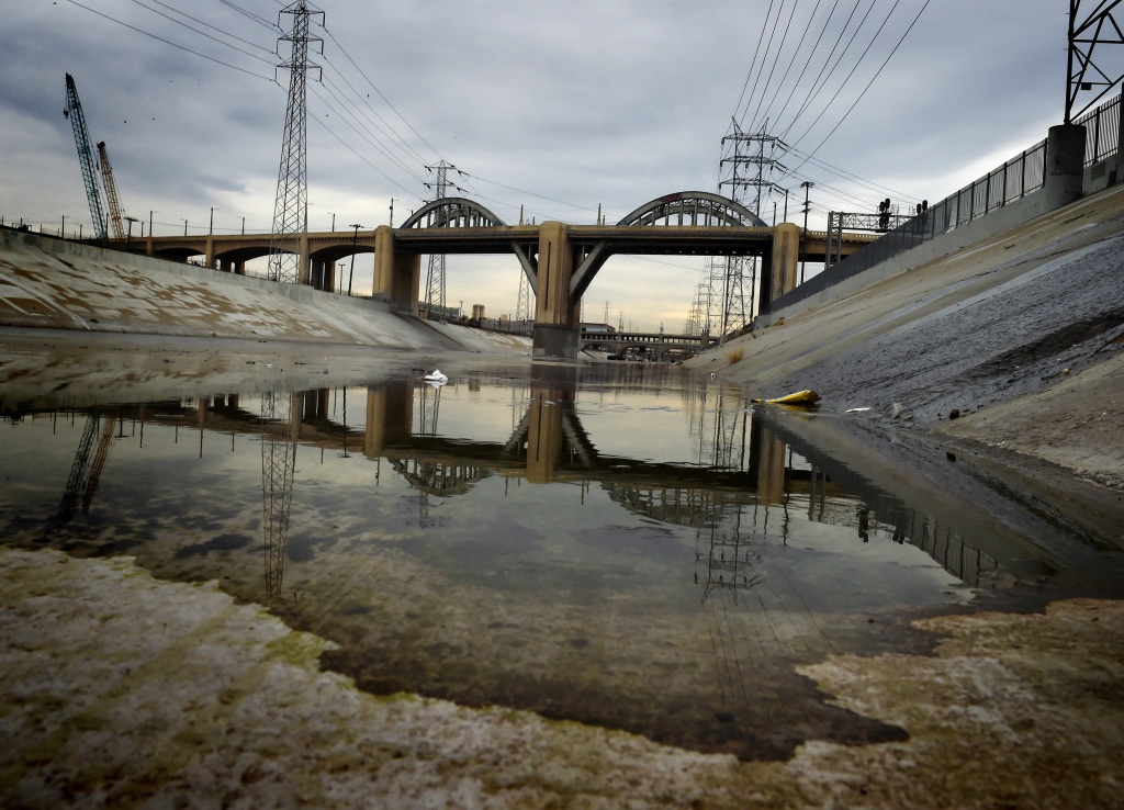 The iconic 6th Street Bridge that connects downtown Los Angeles with its eastern disticts is reflected in the Los Angeles River after its closure to traffic on January 27, 2016.