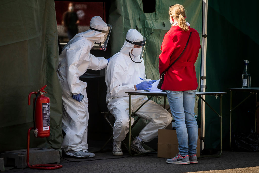 A healthcare worker registers people before getting tested for the coronavirus in Prague on April 23, 2020.