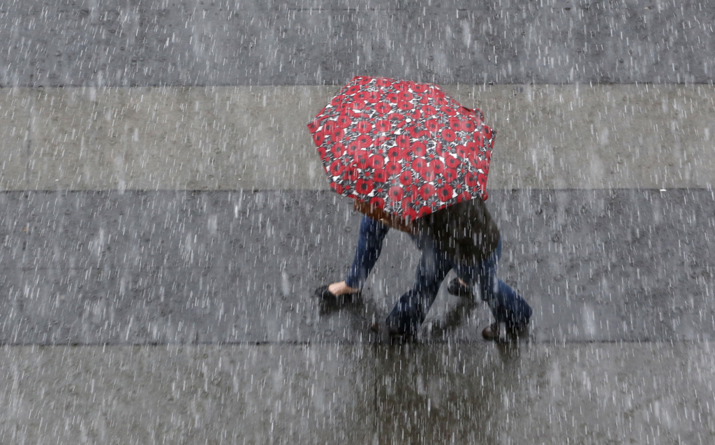 File: An umbrella is shared as rain pelts downtown Sacramento, Calif., Friday, March 4, 2016.