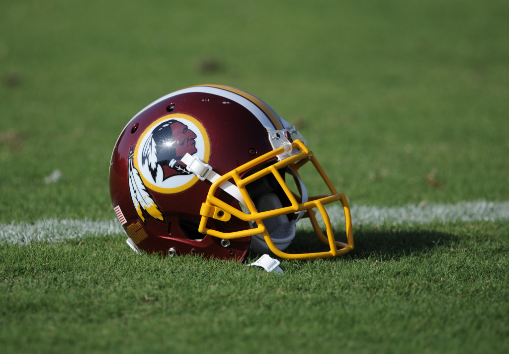 In this file photo, a Washington Redskins football helmet lies on the field during NFL football minicamp. A Supreme Court decision on Monday clears the way for payouts to begin to former players who have been diagnosed brain injuries linked to repeated concussions.