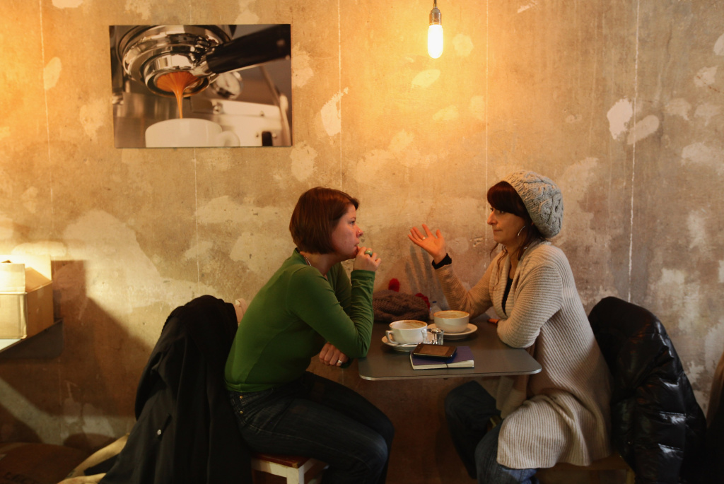 Two young women chat over coffee.