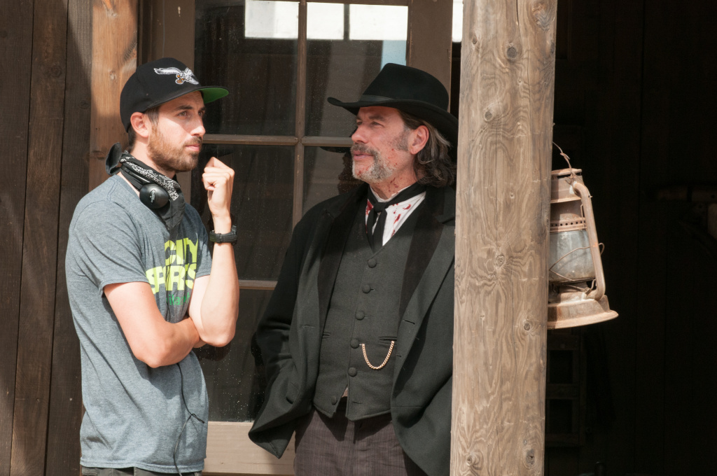Director Ti West and John Travolta on the set of