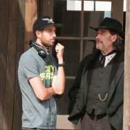 "Director Ti West and John Travolta on the set of ""In a Valley of Violence."""