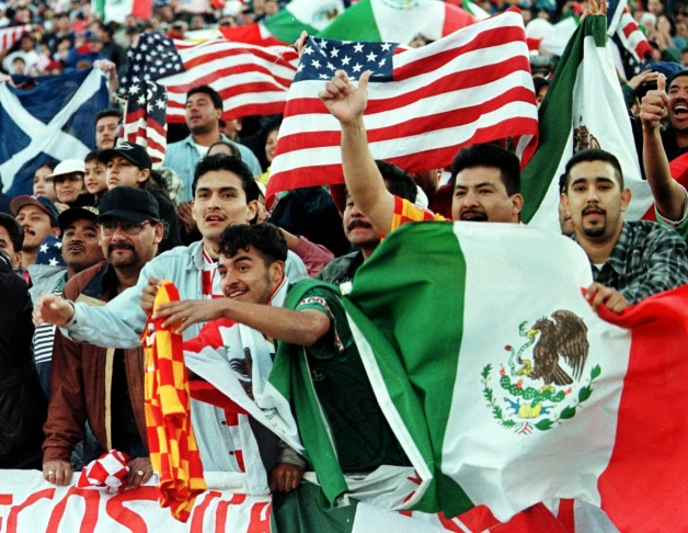 Mexican and US fans wave their nations flags as they cheer for their team.