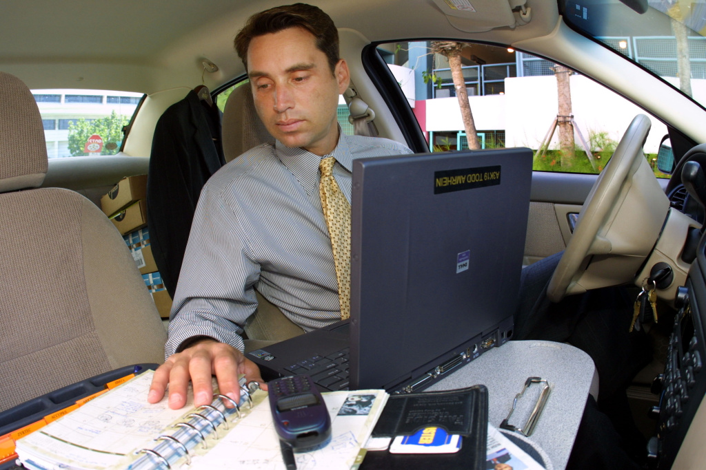 Todd Amrhein, a pharmaceutical salesman, uses his car as an office June 15, 2001 in Miami, FL.