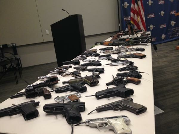 Guns sit on a table during the announcement of a weekend gun buyback.