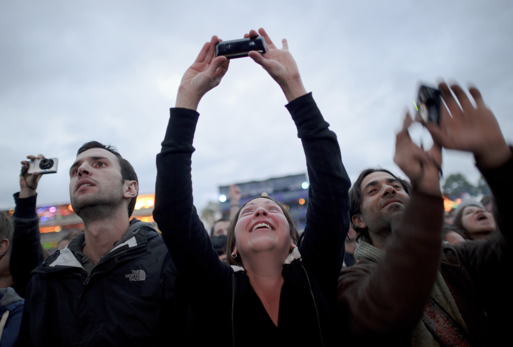 Festival-goers use their cellphones and cameras to record their experiences at the concert.