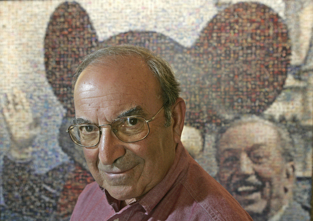 "FILE - In this July 11, 2005 file photo, Martin ""Marty"" Sklar, Imagineering Vice Chairman and Principal Creative Executive, poses in front of a picture of Mickey Mouse and Walt Disney at Disneyland in Anaheim, Calif. Sklar, one of the central figures behind Disney's theme parks around the world, has died.  Sklar had a role in the opening of every Disney park, starting with the original Disneyland in 1955. A Disney statement said he died Thursday, July 27, 2017, at his Hollywood Hills home at age 83.  (AP Photo/Jae C. Hong, File)"