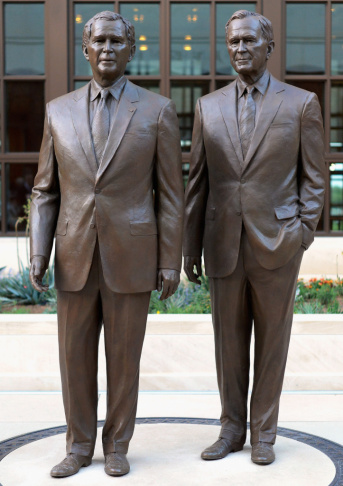 Statues of former Presidents George W. Bush (left) and his father, George H.W. Bush, stand at the George W. Bush Presidential Center on the SMU campus in Dallas, where the George W. Bush Presidential Library and Museum will be dedicated Thursday.
