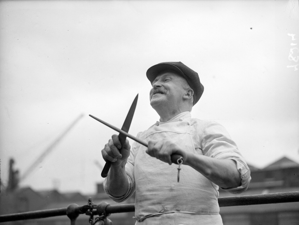 circa 1940:  A ship's cook sharpening a carving knife. His ship is safely in port after being shelled at sea during which time he kept on cooking a mid-day meal.  (Photo by London Express/Getty Images)