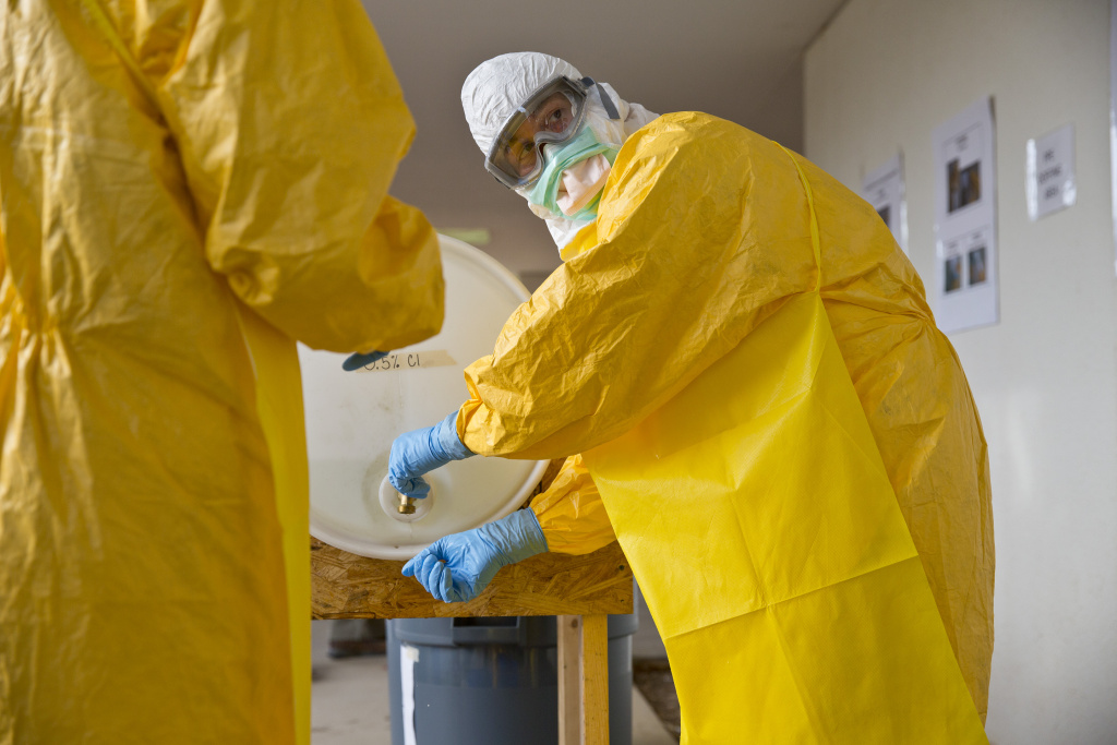 A licensed clinician sanitizes his hands after a simulated training session on Monday, Oct. 6, 2014, in Anniston, Ala.