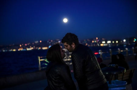 A couple shares a romantic moment as the full moon rises in the background on February 22, 2016.