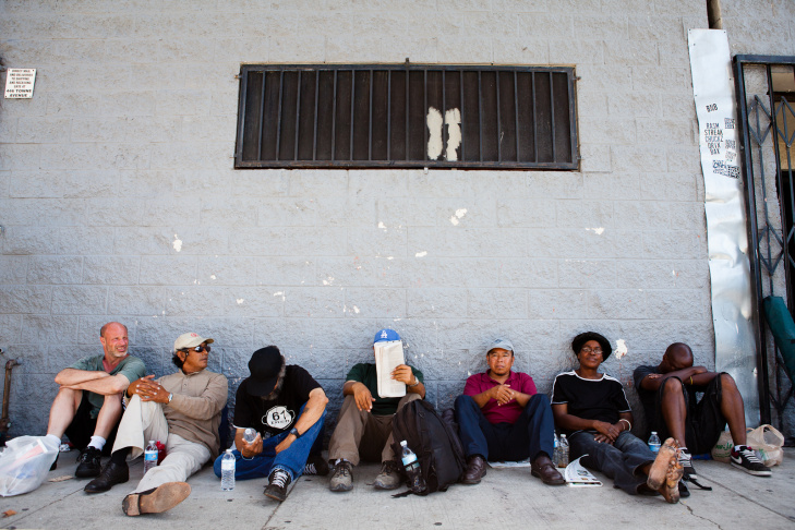 A group of men and women wait in the shade before the start of the annual Humanitarian Day on August 12, 2012.