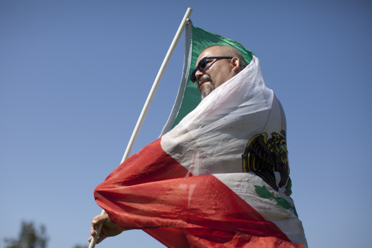 Julio Ramos sets up Mexico Flags while tailgating before the LA Galaxy versus Chivas game at the StubHub Center in Carson. Ramos will be cheering for Mexico during the World Cup, he said.