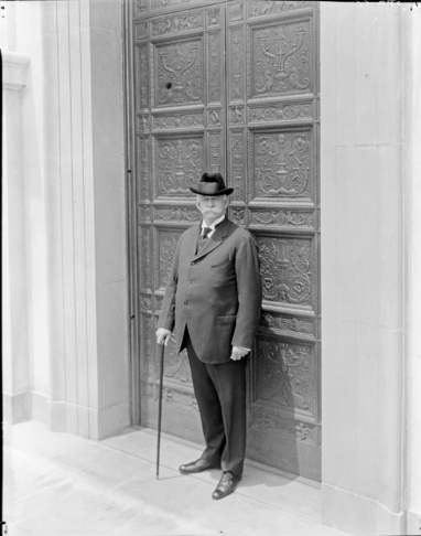 Henry E. Huntington, standing with cane in front of the bronze door to the library building, Henry E. Huntington estate, San Marino, ca. 1927.