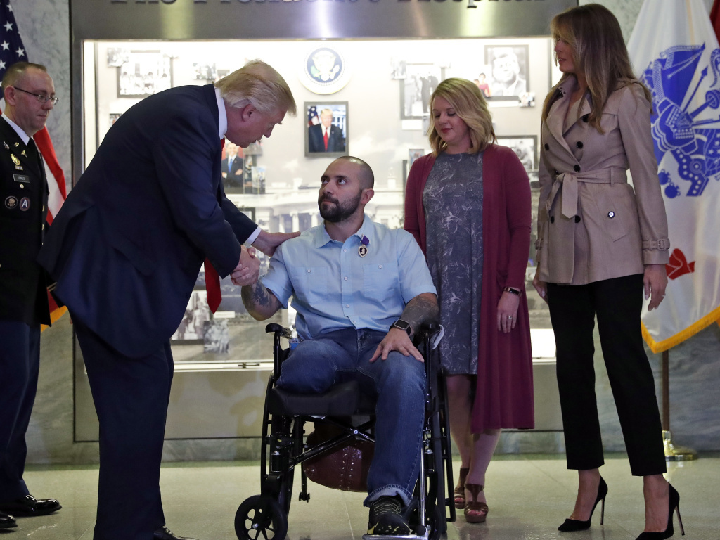 President Donald Trump shakes hands with U.S. Army Sgt. First Class Alvaro Barrientos, after awarding him with a Purple Heart , as first lady Melania Trump, right, stands with Tammy Barrientos second from right, at Walter Reed National Military Medical Center, Saturday.