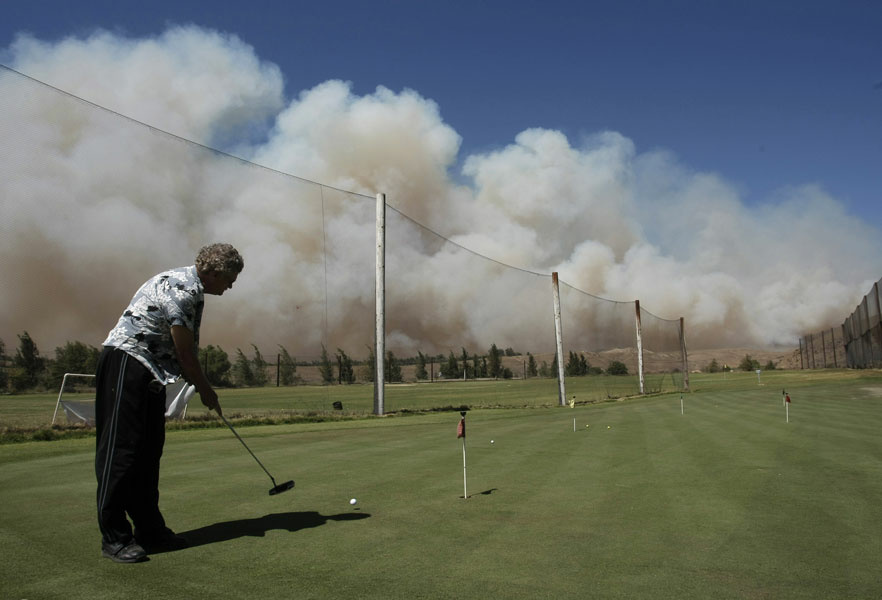 Jim Crawford practices putting at the Rustic Canyon Golf Course as a wildfire burns in the hills of Moorpark, Calif., Tuesday, Sept. 22, 2009.