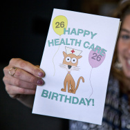 KPCC's Rebecca Plevin holds our downloadable, printable birthday card for your friends and family who are turning 26.