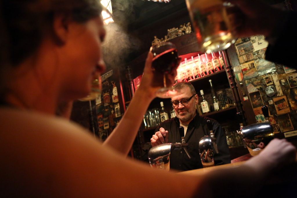 Patrons toast one another as a bartender serves drinks.