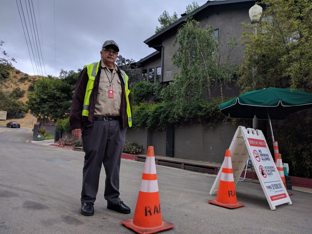 Kenneth Hansen with the LA Department of Recs and Parks stands guard at the former entrance to the Hollywood sign from Beachwood Dr. Since April 18th, the department has had to turn away tourists hoping to get close.