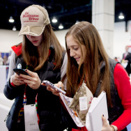 Dalia Wrochesinsky (left) and Robin Saidenberg check their phones during the Conservative Political Action Conference on Thursday.