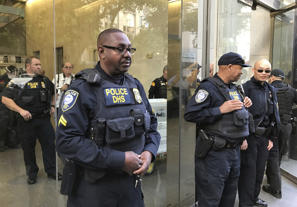 FILE: Officers from the Department of Homeland Security's Federal Protective Service stand guard as people demonstrate outside a federal immigration court in Los Angeles on Monday, March 6, 2017, protesting the arrest of an immigrant who has been ordered deported.
