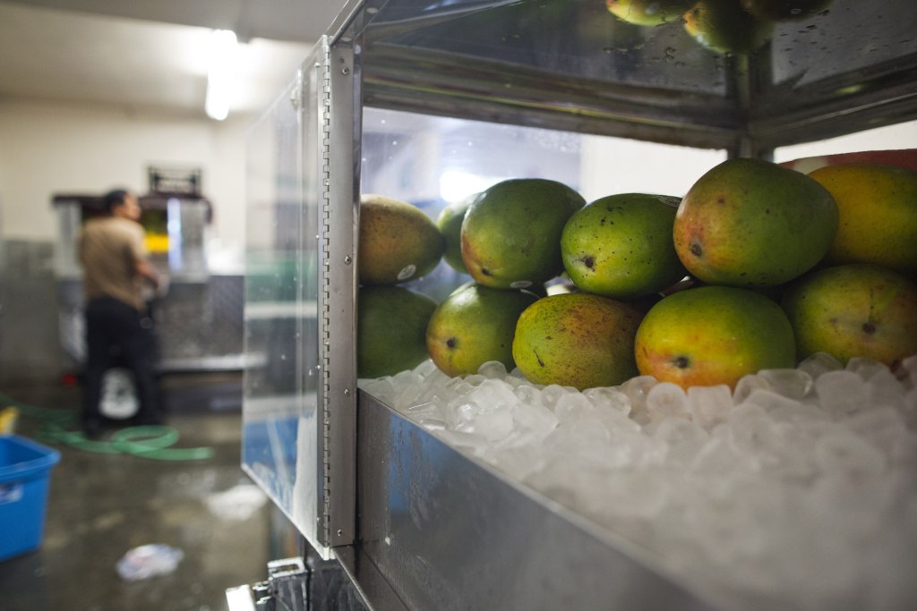 Fruit is prepared for street carts at one of Kareem Cart's commissary locations on South Vermont Avenue on Wednesday morning, Sept. 2, 2015. Having county health department licenses insulates the company from having carts confiscated by LAPD.
