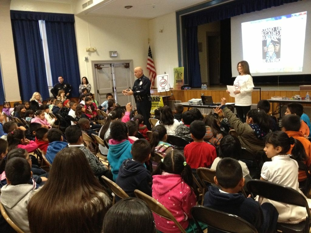 Students listen to an LAPD officer talk about the dangers of bullying at Trinity Street School, a South Los Angeles elementary school.