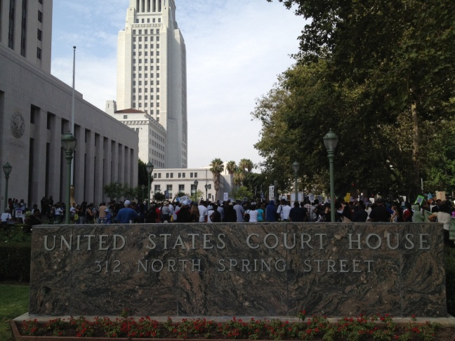 Protesters at a rally in downtown Los Angeles on Saturday hold signs calling for civil rights charges against George Zimmerman, who was acquitted of all charges one week ago in the death of Florida teen Trayvon Martin.